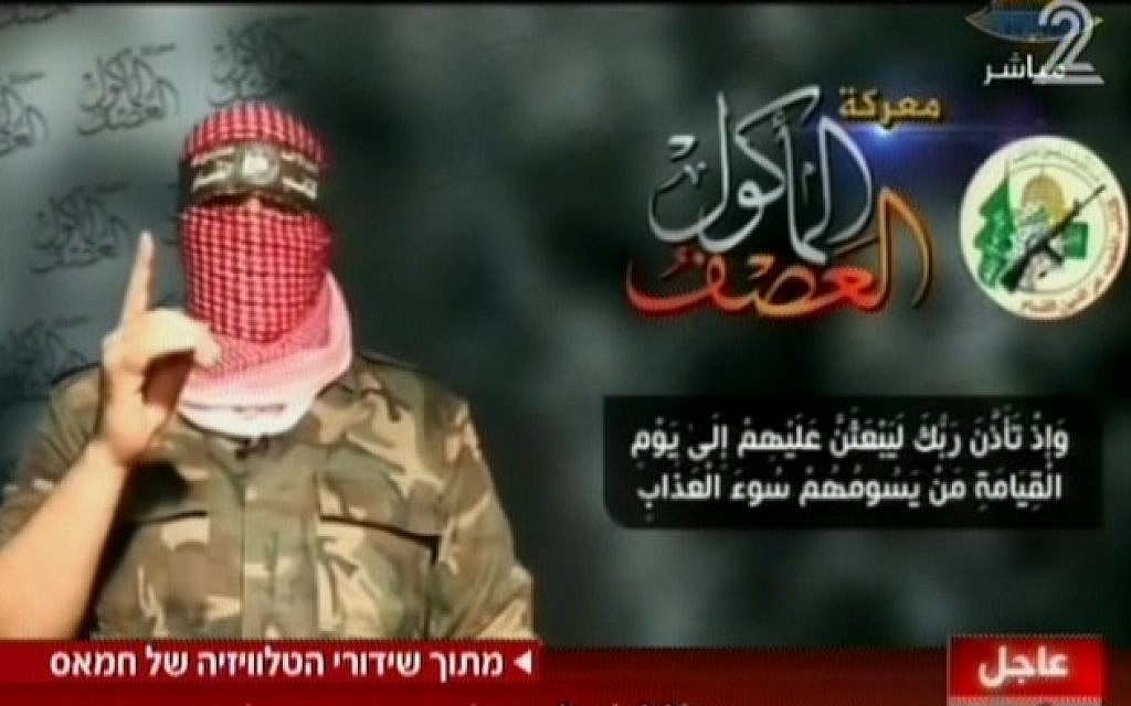 Hamas spokesman Abu Obeida on television Wednesday, August 20, 2014. To the left of the Hamas military-wing logo is text naming the conflict as 'The all-consuming storm.; Below is a passage from the Koran promising divine torture come the Day of Judgement. (Screen capture: Channel 2)
