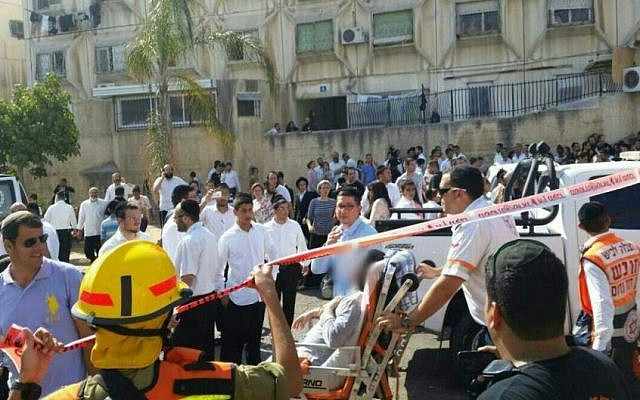 Emergency services evacuate a man injured by shrapnel from a Gaza rocket that hit Ashdod synagogue, August 22, 2014. (Photo credit: Israel Police)