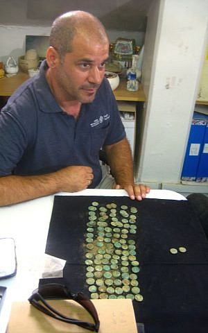 IAA archaeologist Pablo Betzer at the laboratories in Jerusalem's Har Hotzvim, with Jewish Revolt coins set out in front of him. (photo credit: Ilan Ben Zion/Times of Israel staff)