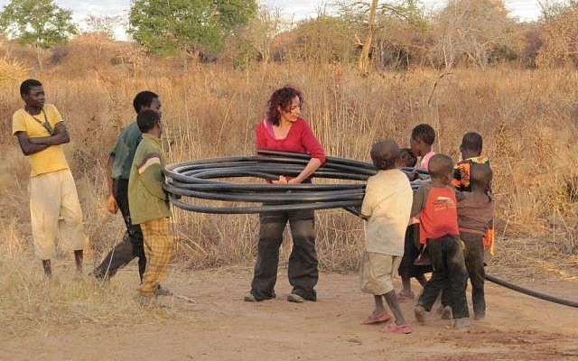 BGU student rolling a water pipe with some locals following a pumping test in Southern Zambia, July 2011. (Photo credit: Noam Weisbrod/Ben-Gurion University of the Negev)