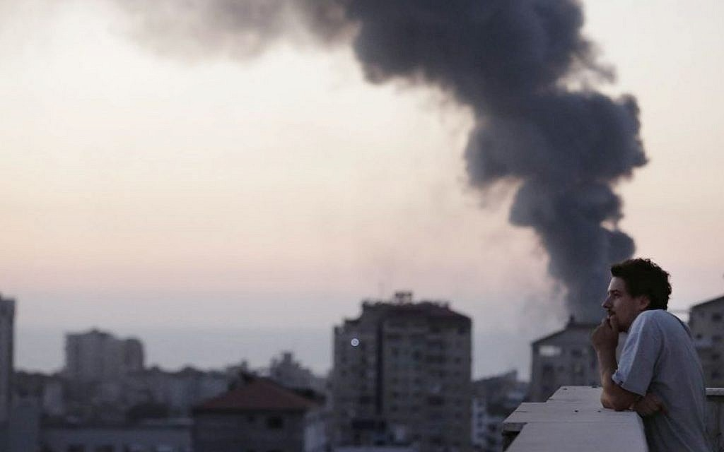 This photo, taken in August 2014, shows Associated Press video journalist Simone Camilli on a balcony overlooking smoke from Israeli Strikes in Gaza City. Camilli was killed on August 13 when working to document an attempt to defuse an Israeli leftover missile in Gaza. (AP Photo/Lefteris Pitarakis)