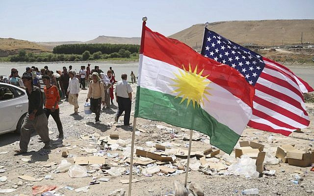 US and Kurdish flags flutter in the wind while displaced Iraqis from the Yazidi community cross the Syria-Iraq border at Feeshkhabour bridge over the Tigris River at Feeshkhabour border point, in northern Iraq, on Sunday, August 10, 2014. (photo credit: AP/Khalid Mohammed)