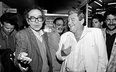 "Israeli producer Menahem Golan, right, and Swiss movie director Jean-Luc Godard, left, speak to the press in Cannes, France, after the screening of Godard's out of competition ""King Lear,"" produced by Golan's Cannon group, May 17, 1987 (Photo credit: Pierre Gleizes/AP, File)"
