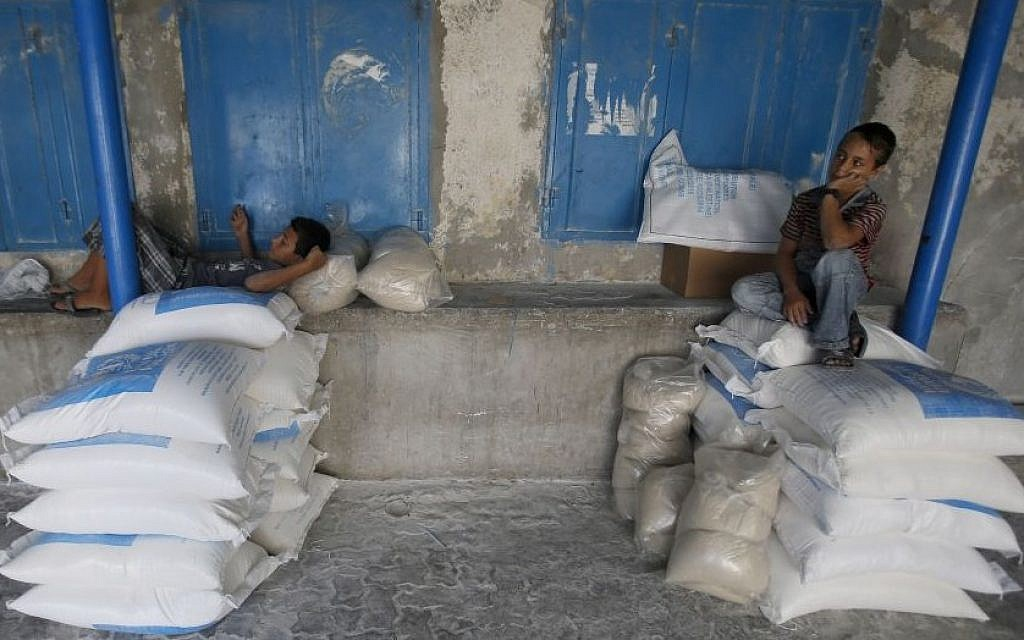 A Palestinian boy sits on bags of flour at a United Nations food aid distribution center, in the Shati refugee camp in Gaza City, Wednesday, Aug. 6, 2014. (Photo credit: AP/Hatem Moussa)