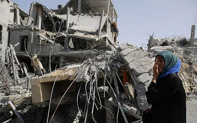 A Palestinian woman cries as she stands near the rubble of her home in Beit Hanoun, Gaza Strip, Friday, Aug. 1, 2014. (photo credit: AP Photo/Hatem Moussa)