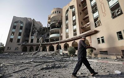 An Islamic University guard inspects the damage to the institution, hit in an overnight Israeli strike, in Gaza City, northern Gaza Strip, Saturday, Aug. 2, 2014. Israel said the institution was used for weapons research and manufacture. (AP Photo/Lefteris Pitarakis)