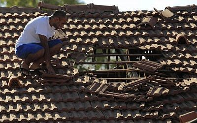 An Israeli man examines the damage to the roof of his house after a rocket fired from Gaza hit in a residential neighborhood of the southern city of Sderot, Friday, August 8, 2014. (photo credit: AP Photo/Tsafrir Abayov)