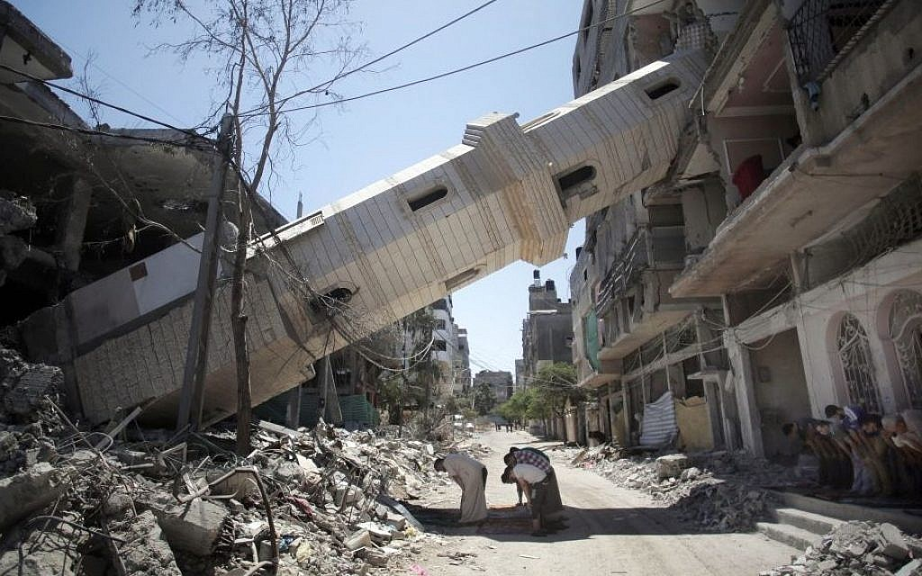 Palestinians attend Friday noon prayers in the shadow of a toppled minaret at a mosque that was hit by Israeli strikes, in Gaza City, Friday, Aug. 8, 2014 (photo credit: AP/Khalil Hamra)