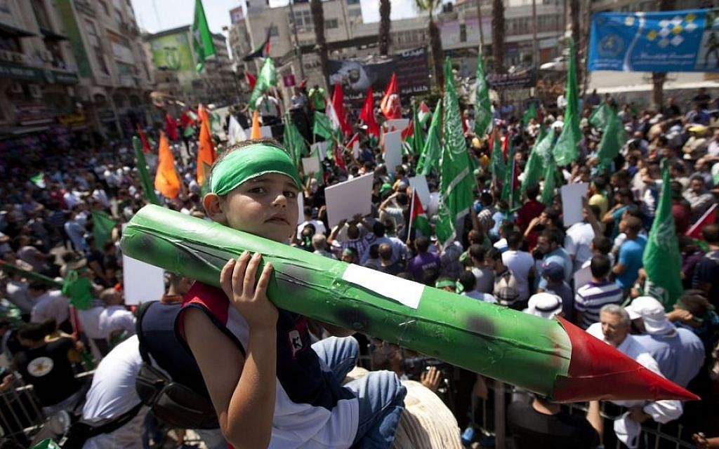 A Palestinian boy holds a model rocket at a Hamas demonstration in the West Bank city of Ramallah, Friday, Aug. 22, 2014. (photo credit: AP Photo/Majdi Mohammed)