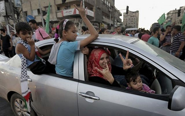 A Palestinian family flashes victory signs as they celebrate the ceasefire between Palestinians and Israelis at the main road in Gaza, in the northern Gaza Strip, Tuesday, Aug. 26, 2014. (photo credit: AP Photo/Adel Hana)
