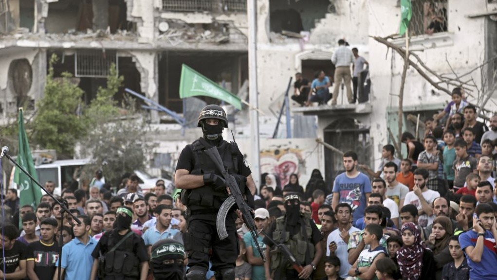 Palestinian gunmen from the military wing of Hamas during what they termed a 'victory rally' amid the debris of destroyed houses in Shejaiya, a Hamas stronghold of Gaza City, Wednesday, August 27, 2014. (photo credit: AP/Adel Hana)