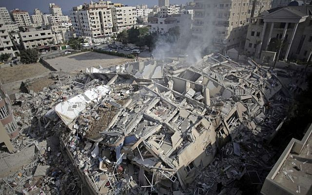 Smoke rises from the rubble of the al-Zafer apartment tower following Israeli airstrikes Saturday that collapsed the 12-story building, in Gaza City, Sunday, August 24, 2014. (photo credit: AP/Khalil Hamra)