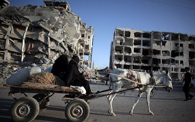 Two Palestinian women ride a donkey cart past the destroyed Nada Towers residential neighborhood in the town of Beit Lahiya, northern Gaza Strip, Monday, Aug. 11, 2014. (photo credit: AP Photo/Khalil Hamra)