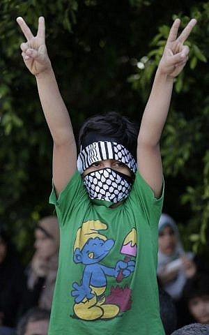 A Palestinian boy flashes the V-sign as he participates in a Hamas rally in Gaza City, Gaza Strip, Thursday, Aug. 7, 2014 (photo credit: AP/Lefteris Pitarakis)
