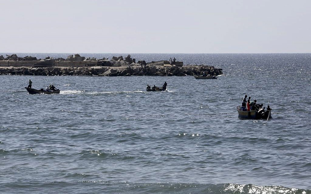 Palestinian fishermen sail to fish as others pull their fishnet at the Mediterranean Sea in Gaza City in the northern Gaza Strip on Thursday, Aug. 7, 2014. (photo credit: AP Photo/Adel Hana)