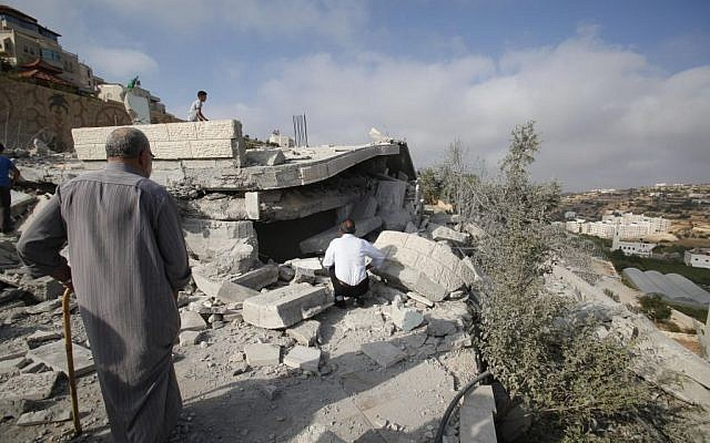Palestinians inspect the rubble of the house of Hussam Kawasme, one of three Palestinians identified by Israel as suspects in the killing of three Israeli teenagers, after it was demolished by the Israeli army in the West Bank city of Hebron, Monday, Aug. 18 , 2014. (photo credit: AP/Nasser Shiyoukhi)