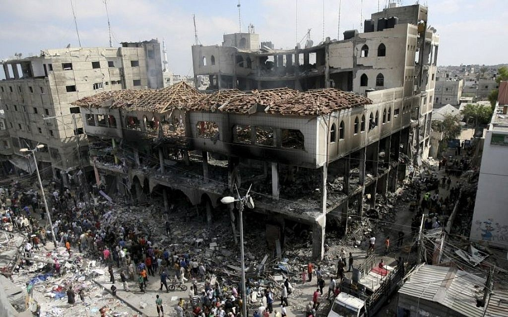 Palestinians inspect the damage to a commercial center after an Israeli strike in Rafah, in the southern Gaza Strip, Aug. 24, 2014. (photo credit: AP Photo/Eyad Baba)