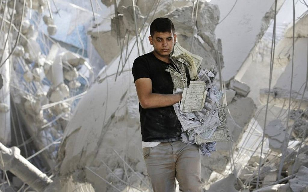 A Palestinian youth carries damaged copies of the Quran, Islam's holy book, found in the rubble of the Imam Al Shafaey mosque, destroyed in an Israeli strike in Gaza City in the northern Gaza Strip on Saturday, Aug. 2, 2014. Israel said it hit five mosques in which rockets were hidden. (Photo credit: AP/Lefteris Pitarakis)
