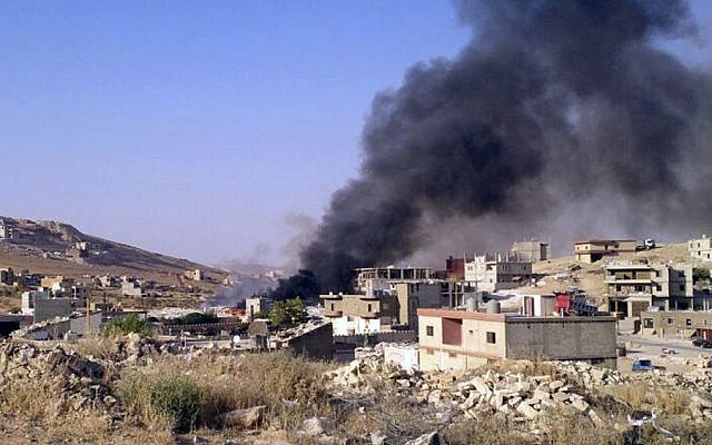 Smoke billows from Arsal, a Sunni Muslim town near the Syrian border in eastern Lebanon, Saturday, Aug 2, 2014. (Photo credit: AP)