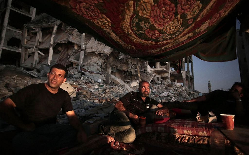 Palestinian Ziad Rizk, center, sits with others in a shelter made of a blanket stretched over four poles next to one of the destroyed al-Nada Towers, where he lost his apartment and clothes shop, in the town of Beit Lahiya, northern Gaza Strip.  (photo credit: AP Photo/Khalil Hamra, File)
