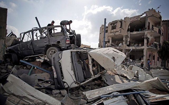 Palestinians search destroyed cars in Rafah's district of Shawkah in the southern Gaza Strip, Tuesday, Aug. 5, 2014. (photo credit: AP/Khalil Hamra)