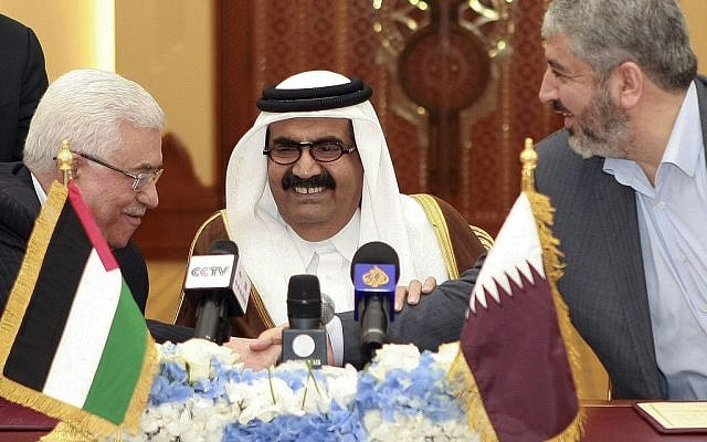 In this Monday, February 6, 2012 file photo, Palestinian President Mahmoud Abbas, left, shakes hands with Hamas leader Khaled Mashaal, right, as the then Emir of Qatar, Sheik Hamad bin Khalifa Al Thani, looks on after signing an agreement in Doha, Qatar. (photo credit: AP/Osama Faisal, File)