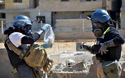 Investigators take samples from sand near a part of a missile that was suspected of carrying chemical agents, according to activists, in the countryside of Ain Terma, Syria, August 28, 2013 (photo credit: AP/United Media Office of Arbeen, File)