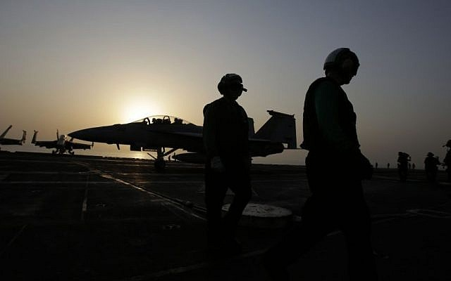 Pilots walk at sunset on the flight deck of the US Navy aircraft carrier USS George H.W. Bush on Sunday, Aug. 10, 2014 in the Persian Gulf. (Photo credit: AP/Hasan Jamali)