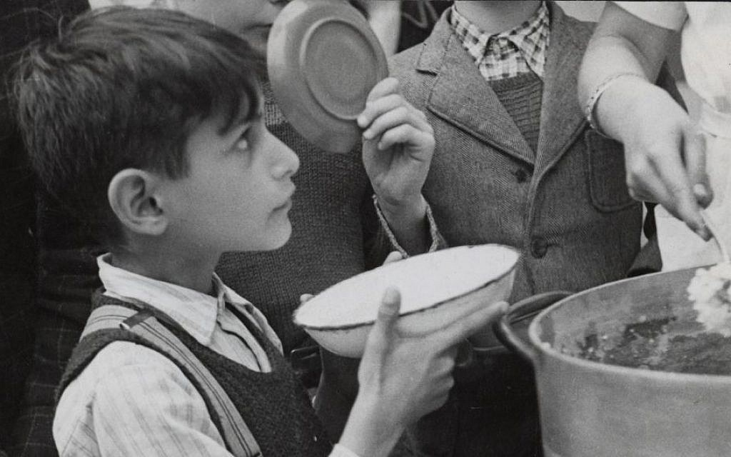 A young refugee who fled Nazi-occupied France to Switzerland through the Alps, is receiving food in a JDC supported facility. He was then sent to a children's home, also supported by JDC. c. 1943 (courtesy)