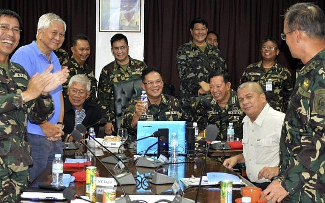 In this photo released by the Armed Forces of the Philippines Public Affairs Office, Philippine Military Chief Gen. Gregorio Catapang, center, reacts after learning about the safe repositioning of Filipino peacekeepers in Golan Heights as they monitor the situation with Philippine Foreign Affairs Secretary Albert Del Rosario, second left, Philippine National Defense Secretary Voltaire Gazmin, third from left seated, at Camp Aguinaldo military headquarters in suburban Quezon city, Philippines on Saturday, Aug. 30, 2014. (photo credit: AP Photo/Armed Forces of the Philippines Public Affairs Office)