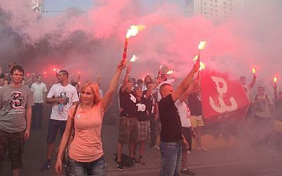 People hold burning flares to commemorate the 70. anniversary of the 1944 Warsaw Uprising in Warsaw, Poland, Friday, Aug. 1, 2014.  (AP Photo/Czarek Sokolowski)