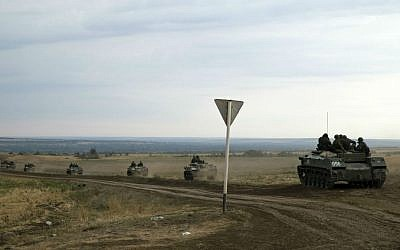 Russian armored personnel carriers move in a field close to the Russia-Ukrainian border near the town of Donetsk, Rostov-on-Don region, Russia, Monday, Aug. 18, 2014. (photo credit: AP/Pavel Golovkin)