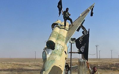 Fighters of the Islamic State waving the group's flag from a damaged display of a government fighter jet following the battle for the Tabqa air base, in Raqqa, Syria, in August 2014. (photo credit: AP/Raqqa Media Center of the Islamic State group)