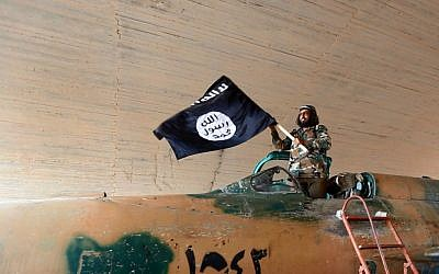 A Fighter of the Islamic State group waving their flag from inside a captured government fighter jet following the battle for the Tabqa air base, in Raqqa, Syria on Sunday. (photo credit: AP/Raqqa Media Center of the Islamic State group)
