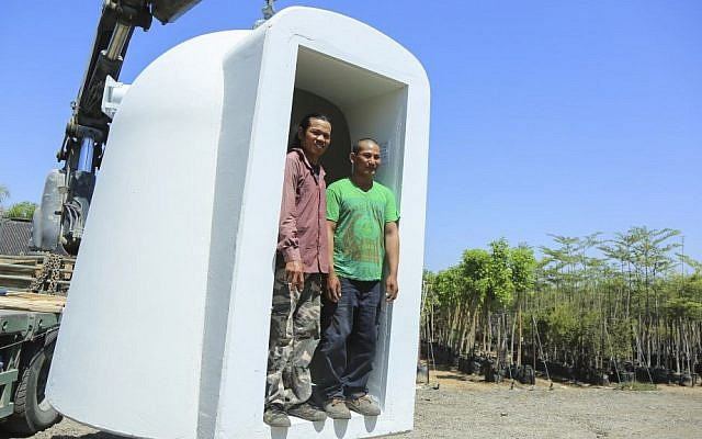 Thai foreign workers standing in a mobile bomb shelter at Moshav Beit HaGadi in the Southern Israel on August 20, 2014. (Edi Israel/Flash90)