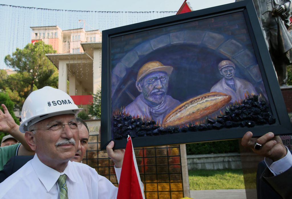 The main opposition candidate in Turkey's Aug. 10 presidential election, Ekmeleddin Ihsanoglu, receives a painting depicting miners as he visits the monument of 301 miners killed in a mine catastrophe in May, in Soma, Turkey, Friday, Aug. 8, 2014 (photo credit: AP/Volkan Yildirim)
