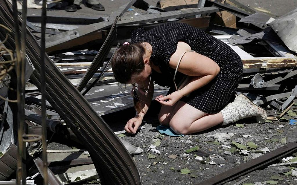 A local woman collects fragments of a shell after night shelling on a local market, in Donetsk, eastern Ukraine, Wednesday, Aug. 6, 2014. Air strikes and artillery fire between pro-Russian separatists and Ukrainian troops in the eastern city of Donetsk have brought the violence closer than ever to the city center, as Kiev's forces move in on the rebel stronghold. (AP Photo/Sergei Grits)