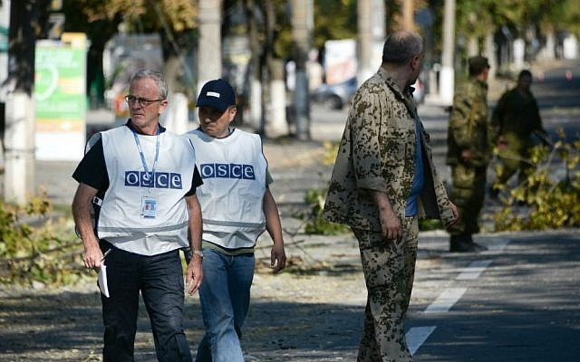 Members of the Organization for Security and Co-operation in Europe examine the scene of a shelling in the town of Donetsk, eastern Ukraine, Wednesday, Aug. 27, 2014. (photo credit: AP/Mstislav Chernov)