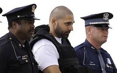FILE - In this Aug. 26, 2010 file photo, Elias Abuelazam is escorted by authorities after arriving on a flight in Flint, Mich. Abuelazam, serving a life sentence for murder in a series of stabbings in the Flint area is suing to be deported to Israel, his home country. (photo credit: AP Photo/Paul Sancya)