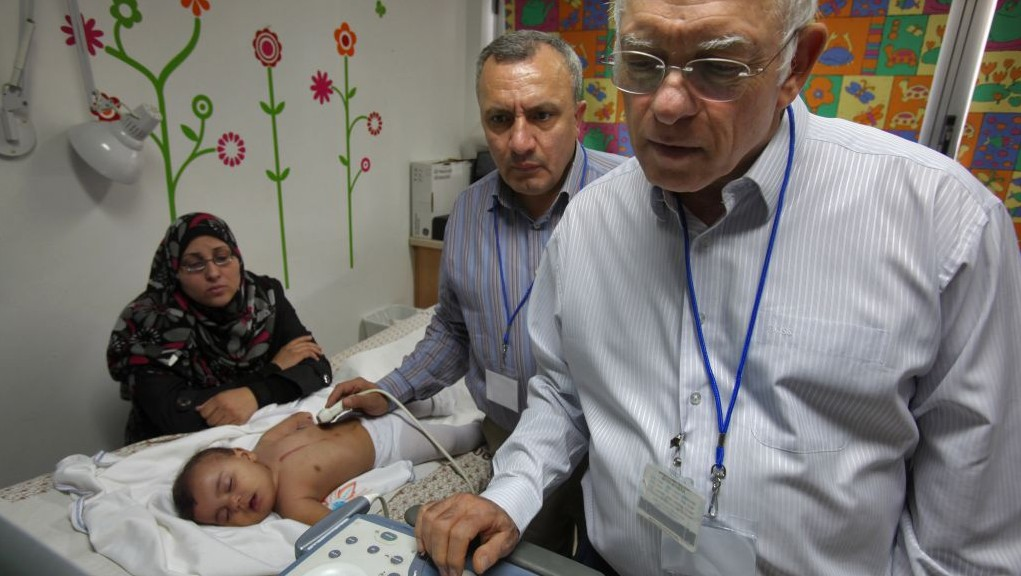 Paediatric cardiologists Dr. Akiva Tamir, of Wolfson Medical Center, and Dr. Omar Assali, of Nablus's Rafidiya hospital, preform a follow-up echo-cardiograph examination together on a Palestinian patient at Wolfson hospitals clinic photo credit: David Silverman/Flash90)
