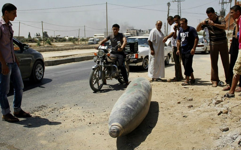 Palestinians look at an unexploded munition on a street in Deir El-Balah in the central Gaza Strip on August 01, 2014. (photo credit: Mostafa Ashqar/FLASH90)