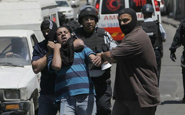 Undercover Israeli police officers detain a Palestinian suspected of throwing stones in the East Jerusalem neighborhood of Wadi al-Joz, August 1, 2014. (photo credit: Sliman Khader/Flash90)