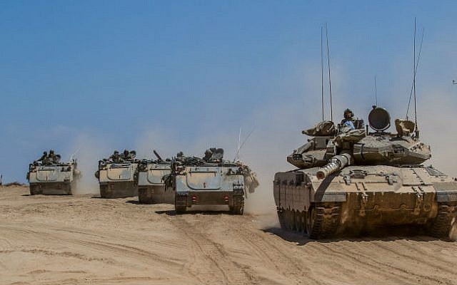 Israeli tanks and armored personnel carriers (APCs) drive at an unspecified location next to the Israel-Gaza Strip border, after pulling back from the Gaza Strip on August 3, 2014. (photo credit: Flash90)