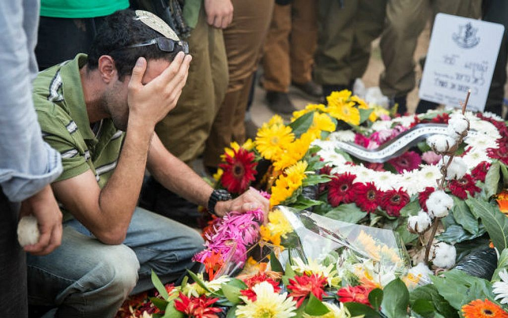 Friends and relatives seen mourning over the grave of Staff Sergeant Liel Gidoni, during his funeral at the Mount Herzl military cemetery in Jerusalem, on August 3, 2014. Gideoni was killed in combat on Friday in the Gaza Strip. (photo credit: Hadas Parush/Flash90)