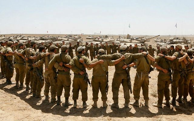 Israeli soldiers sing as they embrace each other at a staging area in southern Israel near the border with Gaza, as Israeli forces prepare to pull back from the area, on August 06, 2014. (photo credit: Miriam Alster/Flash90)