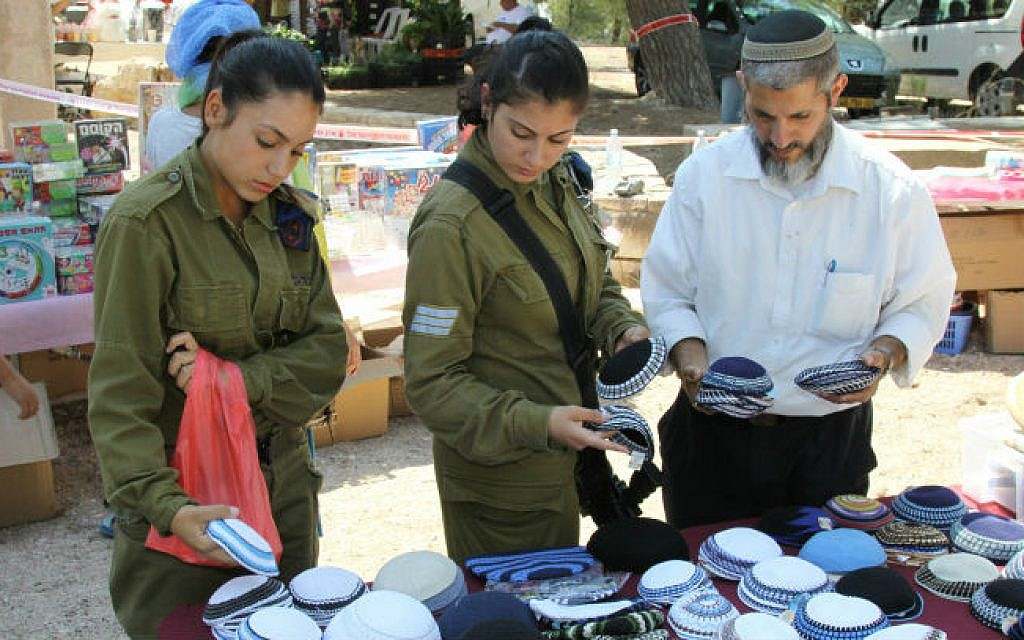 Israelis soldiers shop at a market organized in benefit of the businesses in Southern Israel, in the Israeli settlement of Har Gilo on August 15, 2014 (photo credit: Gershon Elinson/Flash90)