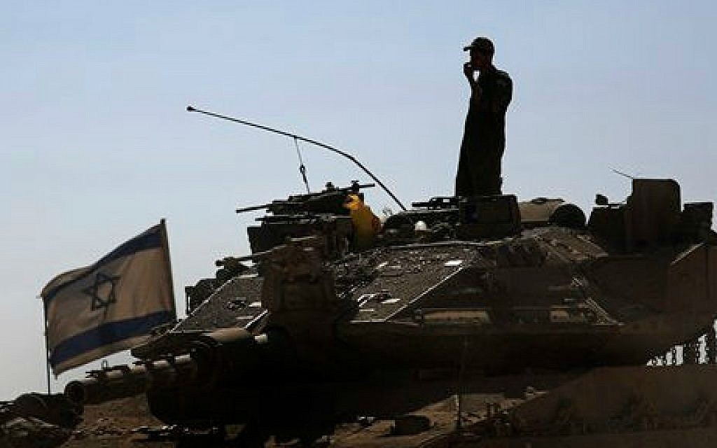 An Israeli soldier standing on top of a tank in a staging area near the Israel Gaza border, Saturday, August 2, 2014 (photo: AP/Tsafrir Abayov)