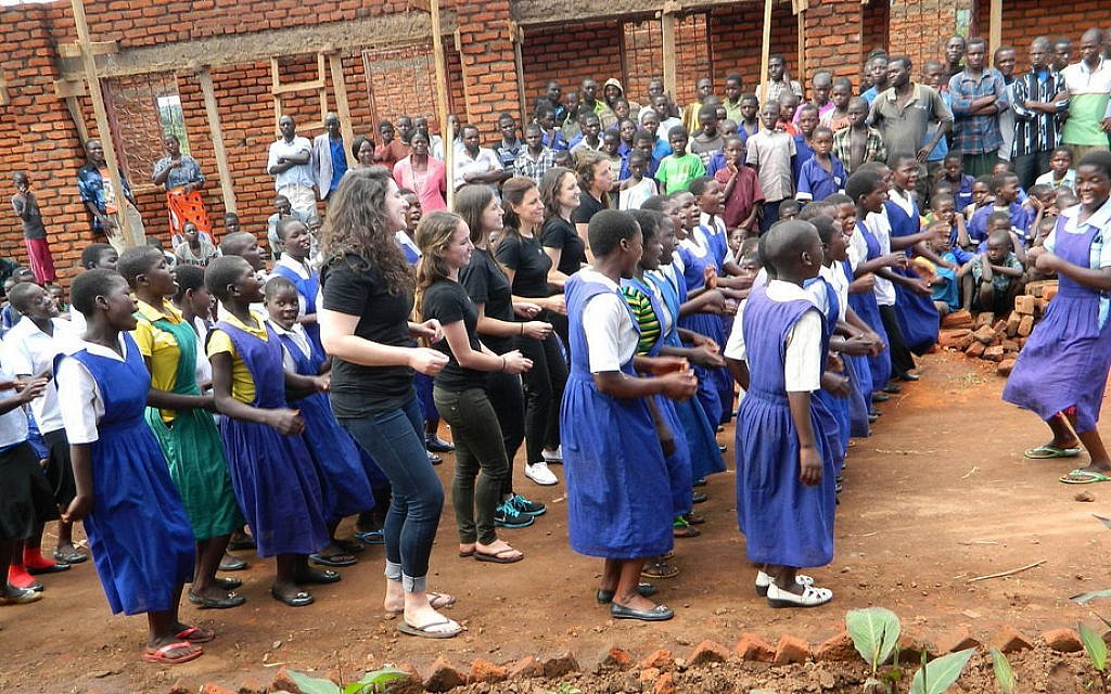Members of the Innovation Africa team dance with students at N'gozi Primary School, Malawi before the lights are switched on for the first time in their classrooms. (Courtesy)