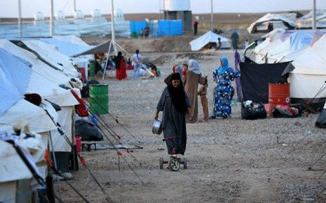 An Iraqi woman, who fled violence in the northern city of Tal Afar, walks through the Bahrka camp, 10 km west of Arbil in the autonomous Kurdistan region, on August 30, 2014 (photo credit: AFP/ Safin Hamed)