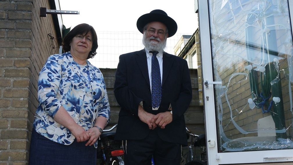 Rabbi Binyomin Jacobs and his wife, Bluma, by the glass window of their home damaged in an attack on July 17, 2014. (Cnaan Liphshiz/JTA)